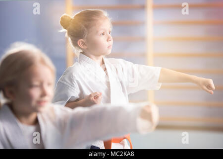 Girl in white kimono practicing karate during extra-curricular class at school - Stock Photo