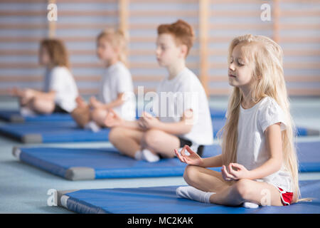 Group of children sitting in lotus pose on blue mats during a yoga class - Stock Photo