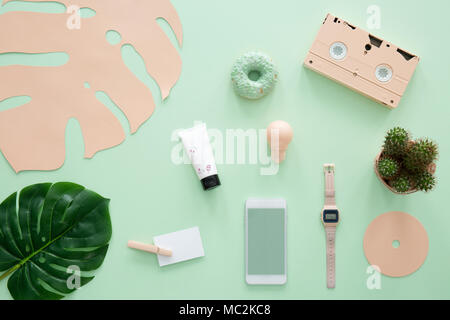 Pink cassette, smartphone and watch on mint background with green leaf - Stock Photo