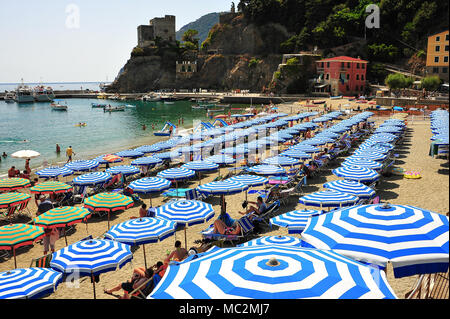 Symetrical rows of blue and white umbrellas on a sandy beach, Monterosso al Mare in Italy - Stock Photo