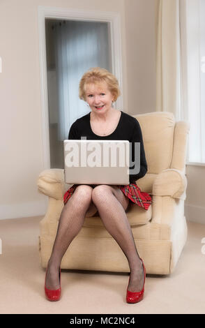 Mature woman sitting in a comfortable chair using a laptop computer - Stock Photo