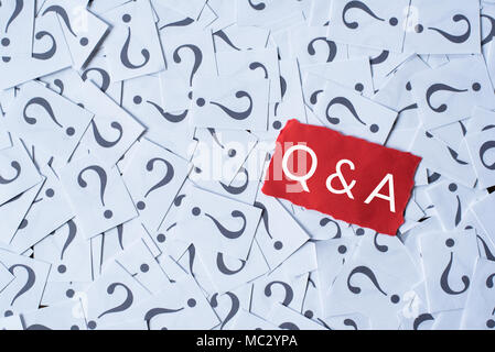 question mark on white paper and Q&A on red paper. questions and answer concept - Stock Photo