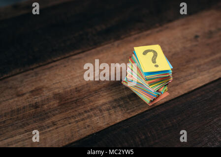 multicolored paper with QUESTION MARK on a wooden table background. questions,mystery and diversity concept. FAQ and Q&A background concept - Stock Photo