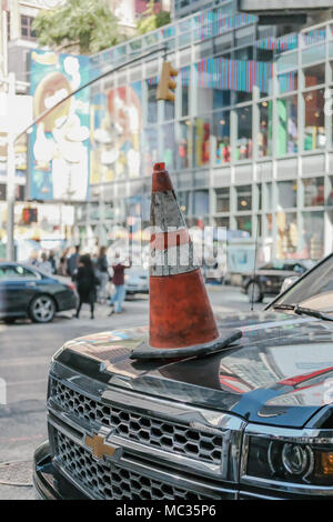 Single traffic cone seen illegally placed on a bonnet of an SUV vehicle which has been parked in a No Parking zone in central Manhattan. - Stock Photo