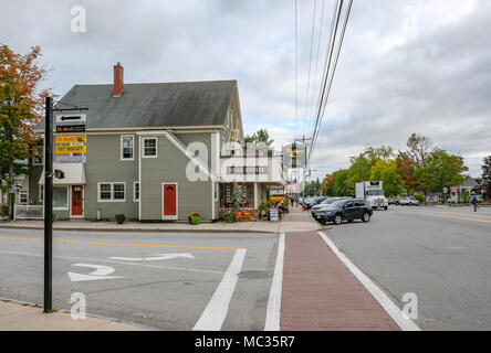 Exterior view of an empty side street junction showing a timber-built Real Estate building together with a parking lot at a road junction. - Stock Photo