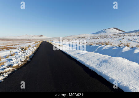 Deserted snowy road in Scottish Highlands - Stock Photo