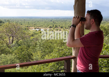 A man with binoculars looks into Victoria Falls National Park seen from Victoria Falls Safari Lodge in Zimbabwe. - Stock Photo