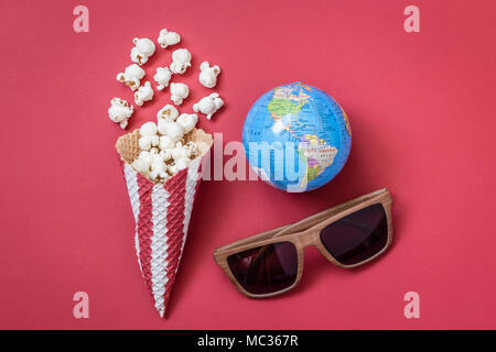 Flat lay of popcorn with ice cream cone, 3d glasses and globe on red background minimal cinema creative concept - Stock Photo