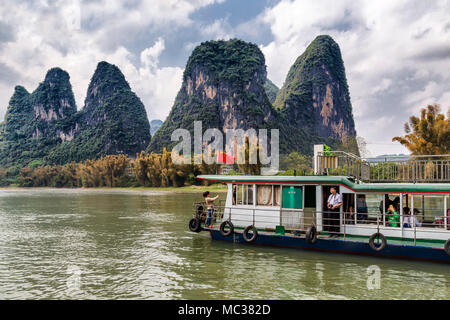 A tourist boat carries passengers along the Li River, Yanshuo, China. They look out at the unusual formation of the karst mountains. - Stock Photo