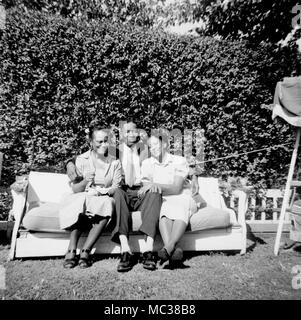 A trio of adults on a backyard couch in California, ca. 1956. - Stock Photo