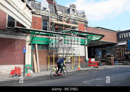 Cyclist cycling past men working on scaffold on old market building at West Smithfield, London UK   KATHY DEWITT - Stock Photo