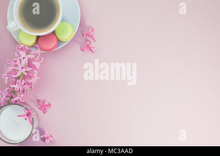 Creative flat lay photo of coffee cup with flowers, candle and macaroons with copy space on pink background minimal style - Stock Photo