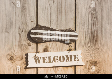 Wooden welcome sign in rustic style hanging on plank door - Stock Photo