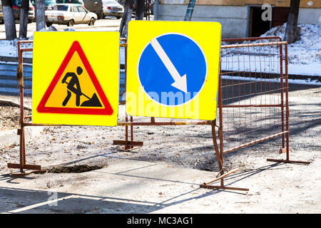 Road work and detour signs on the city road in winter sunny day - Stock Photo
