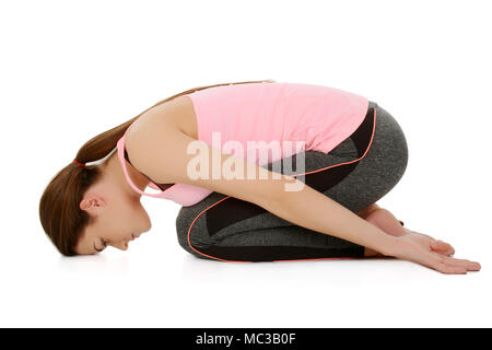 A young white girl performs yoga asanas Child's pose ,on sanskrit Balasana .Best asana for lumbal pain and relax position. - Stock Photo