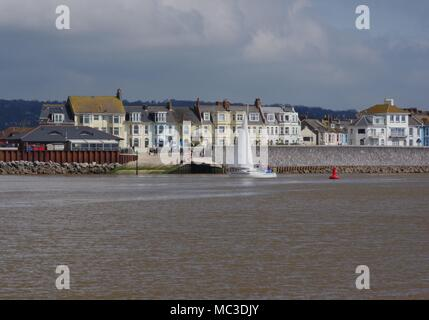 Victorian Architecture of Exmouths Seafront, with White Sailing Yacht Heading into the Exe Estuary. South devon, UK. April, 2018. - Stock Photo