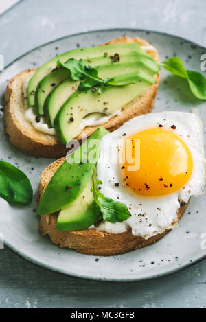 Avocado Sandwich with Fried Egg - sliced avocado and  egg on toasted bread with arugula for healthy breakfast or snack. - Stock Photo