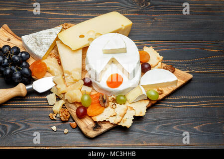 Brie cheese on a wooden Board with fresh figs and grapes - Stock Photo