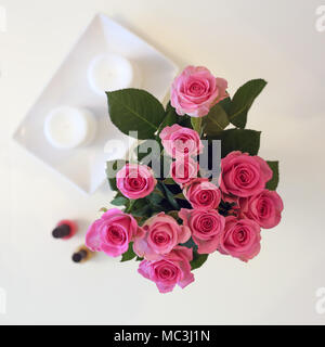 A Bunch of pink flowers in a vase. The photo is taken from above (flatlay). In addition to roses there is white candles and two nail polishes. - Stock Photo