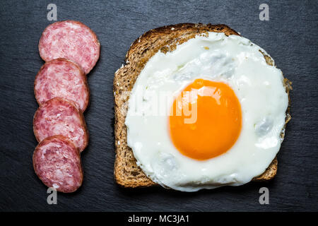 Fried egg on a toast and silced sausage. Florianopolis, Santa Catarina, Brazil. - Stock Photo
