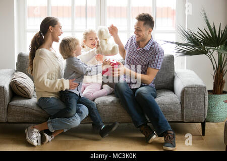 Happy family with kids congratulating excited dad with fathers d - Stock Photo