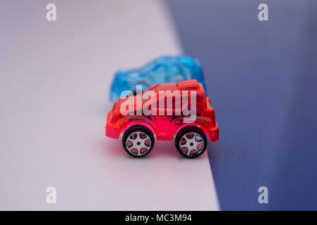 transparent red white and blue toy cars on flag style background - Stock Photo