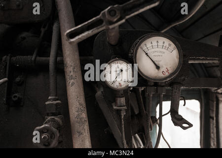 Details of interior of abandoned old rusty soviet locomotive at platform. Two braking vintage manometers and rusty pipes. Written in russian on white  - Stock Photo