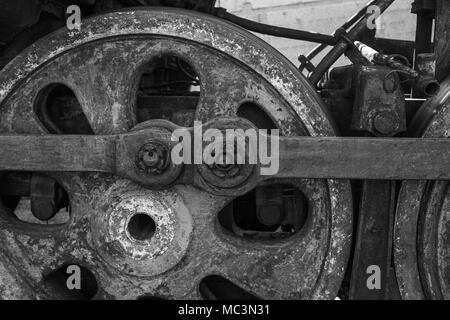 Closeup view of weathered wheels of abandoned old rusty soviet locomotive at platform. Horizontal black and white photography. - Stock Photo