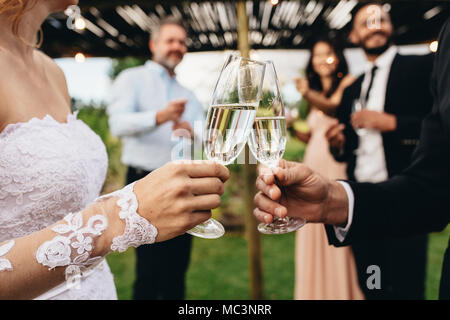 Close up of bride and groom toasting champagne glasses at wedding party. Newlyweds clinking glasses at wedding reception outside. - Stock Photo