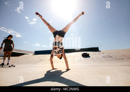Girls doings stunts at skate park. Women doing a flip with friend riding on a long board. - Stock Photo