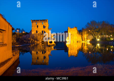 The ruins of Borghetto sul Mincio towers bridge on the river, with the pedestrial lane. Veneto region, Italy. Night view at blue hour. - Stock Photo