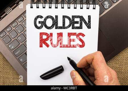 Word writing text Golden Rules. Business concept for Regulation Principles Core Purpose Plan Norm Policy Statement written by Man Holding Pen Notebook - Stock Photo