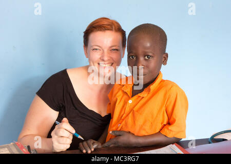Uganda. June 13 2017. A smiling Ugandan boy with a white foreign missionary doctor at the Primary school in Kayanja. - Stock Photo