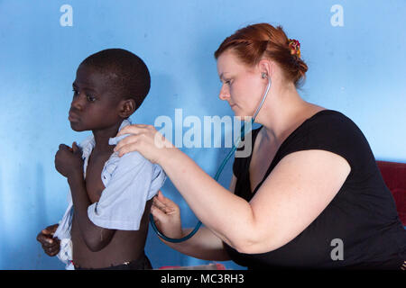 Uganda. June 13 2017. A white foreign missionary doctor examining a child patient at a primary school. - Stock Photo