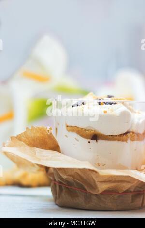 Tiramisu dessert in transparent plastic cup; with copy space - Stock Photo