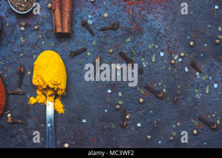 Tea spoon full of curry spice, on black background with copy space - Stock Photo