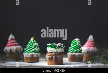 Decorated christmas cupcakes, on wooden background with copy space - Stock Photo