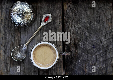 Turkish coffee in a traditional cup and teaspoon on a wooden background - Stock Photo