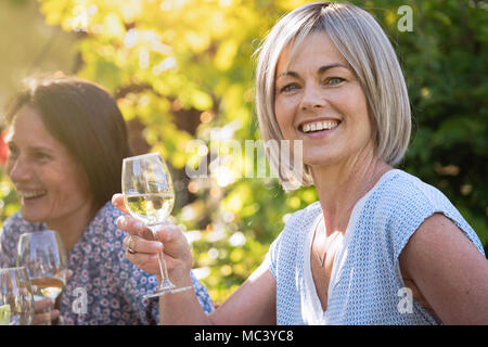 Group of friends gathered around a table in a garden to have a good time together. Focus on a beautiful woman looking at camera a drink at hand - Stock Photo