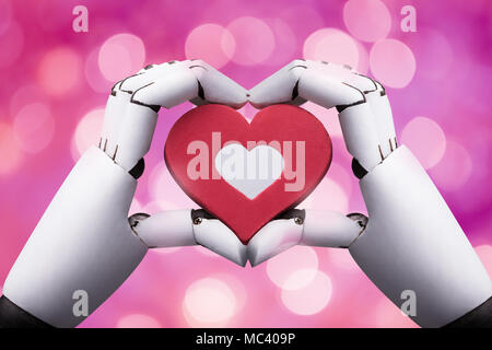 Close-up Of A Robotic Hand Holding Red Heart Against Bokeh Background - Stock Photo