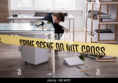 Close-up Of Yellow Crime Scene Tape In Front Of Investigator Collecting Evidence - Stock Photo