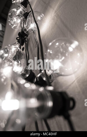 Decorative light bulbs against wall background. Bottom view. Candid shallow DOF. - Stock Photo