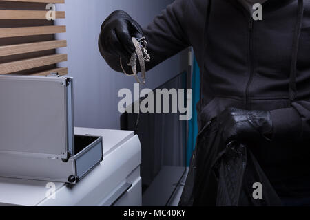 Close-up Of A Robber's Hand Wearing Gloves Stealing Jewelry From Box - Stock Photo