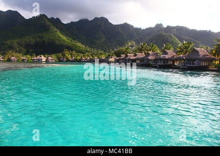 View towards the a bay in Moorea, with turquoise tropical water & bungalows over the sea. French Polynesia, South Pacific. - Stock Photo