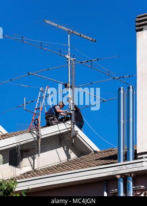 workers on the roof repair TV aerial - Stock Photo