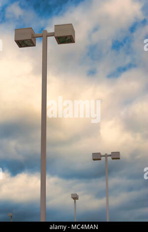 Looking up at light poles in parking lot against a cloudy sky in the black and white photograph with copyspace - Stock Photo