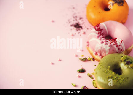 Colorful donuts with icing on pastel pink background. Sweet orange, green, pink doughnuts with pistachio, chocolate. Flat lay, top view, copy space - Stock Photo