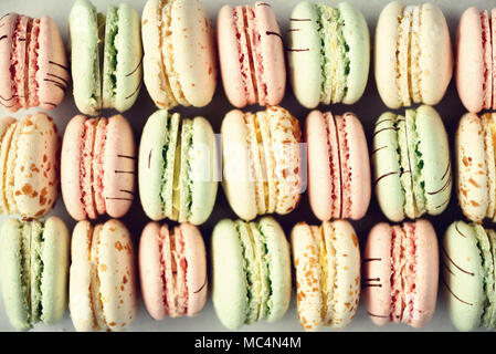Colorful french macaroons flat lay. Pastel colors pink, green, yellow macarons with copy space, top view. Holidays and celebrations concept. Sweet gift for woman, girl - Stock Photo