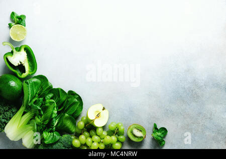 Organic green vegetables and fruits on grey background. Copy space, flat lay, top view. Green apple, lettuce, zucchini, cucumber, avocado, kale, lime, kiwi, grapes, banana, broccoli - Stock Photo