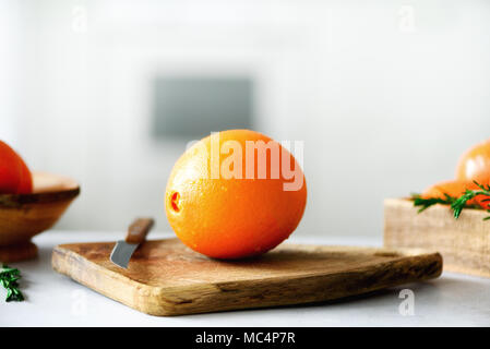 Citrus fruits background. Fresh fruits, rosemary. Big orange fruit with water drops, knife, wooden cutting board on design white kitchen. Copy space - Stock Photo